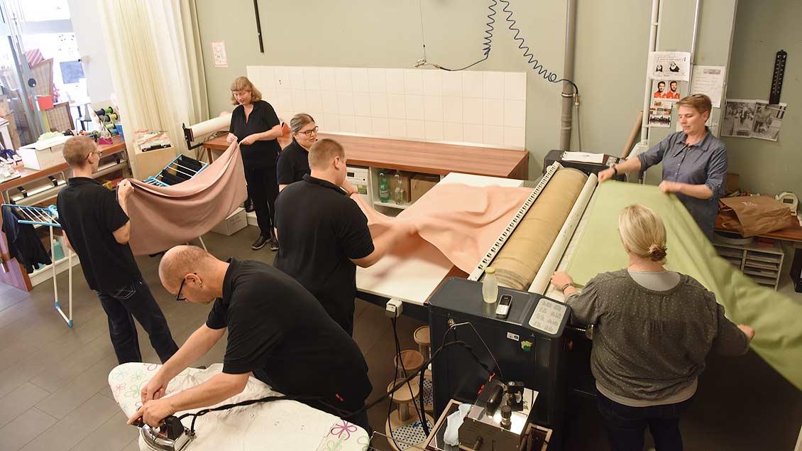 Teamwork in der Mangelstube: Die Menschen mit Behinderung arbeiten hier Hand in Hand. | Foto: Michael Bönte