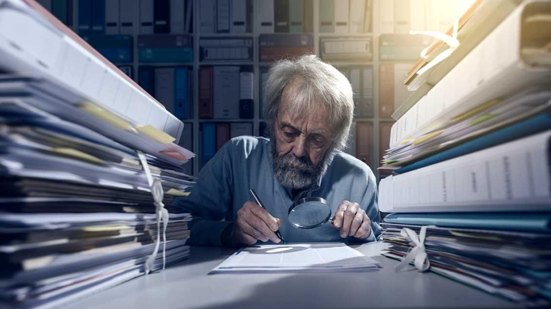 Ein alter Mann mit Lupe studiert Akten.