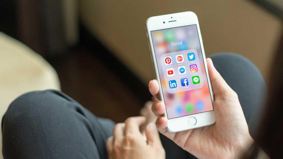 Smartphone in der Hand mit verschiedenen sozialen Netzwerken.
