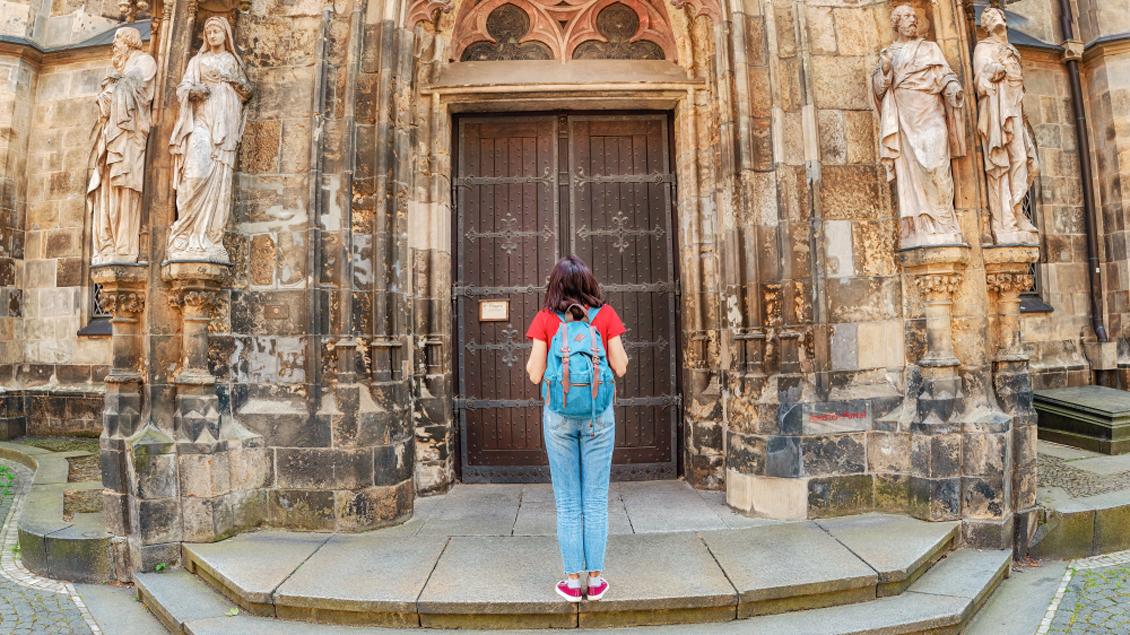 Eine Frau steht vor einer geschlossenen Kirchentür.