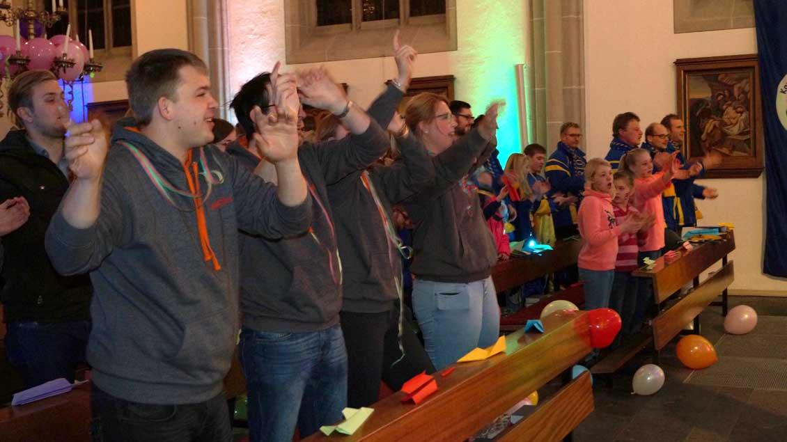 Jugendliche feiern zur Karnevalsmusik im Gottesdienst.