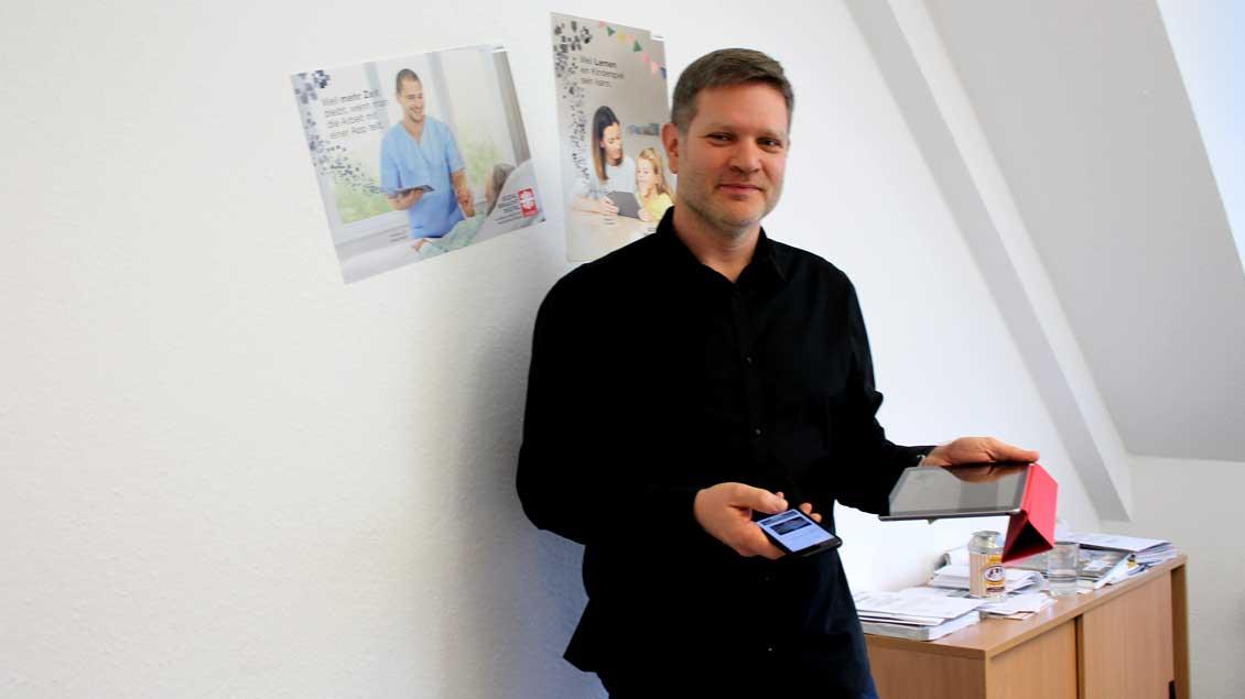 Rüdiger Dreier mit Smartphone und Tablet in der Hand.