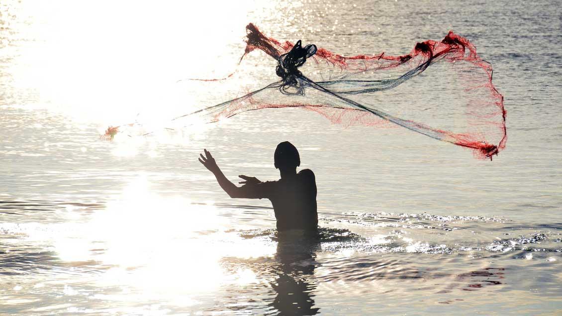 Ein Fischer steht im Wasser und wirft ein Netz aus.