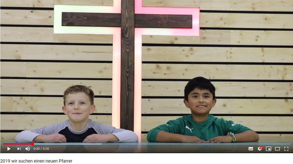 Zwei Messdiener sitzen vor einem bunt beleuchteten Kreuz.