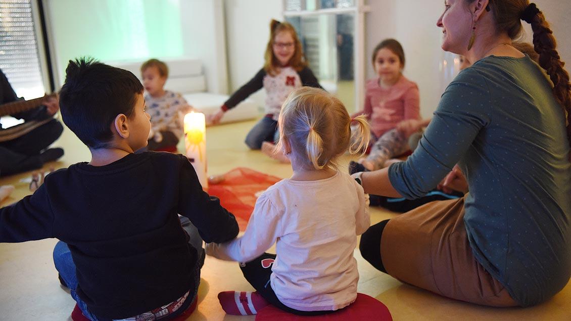 Kinder sitzen mit Erzieherinnen im Kreis und halten sich an den Händen. In der Mitte brennt eine Kerze.