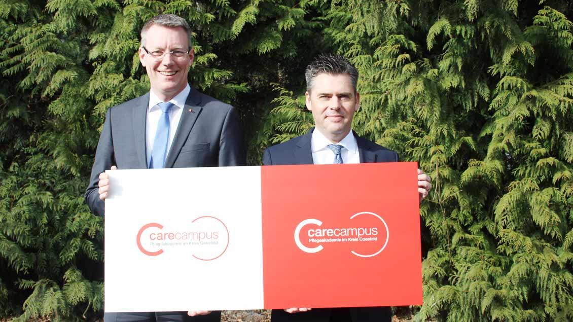 Christian Germing, Vorstand des Caritasverbands für den Kreis Coesfeld (links), und Mark Lönnies, Geschäftsführer der Christophorus-Kliniken, präsentieren das Logo der Pflegeakademie.