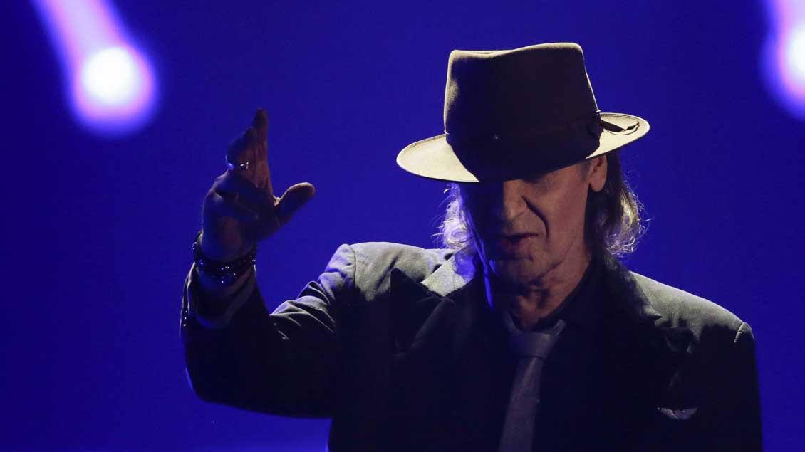 Musiker Udo Lindenberg im farbigen Scheinwerferlicht. Den Hut tief im Gesicht, deutet er mit der rechten Hand nach oben.