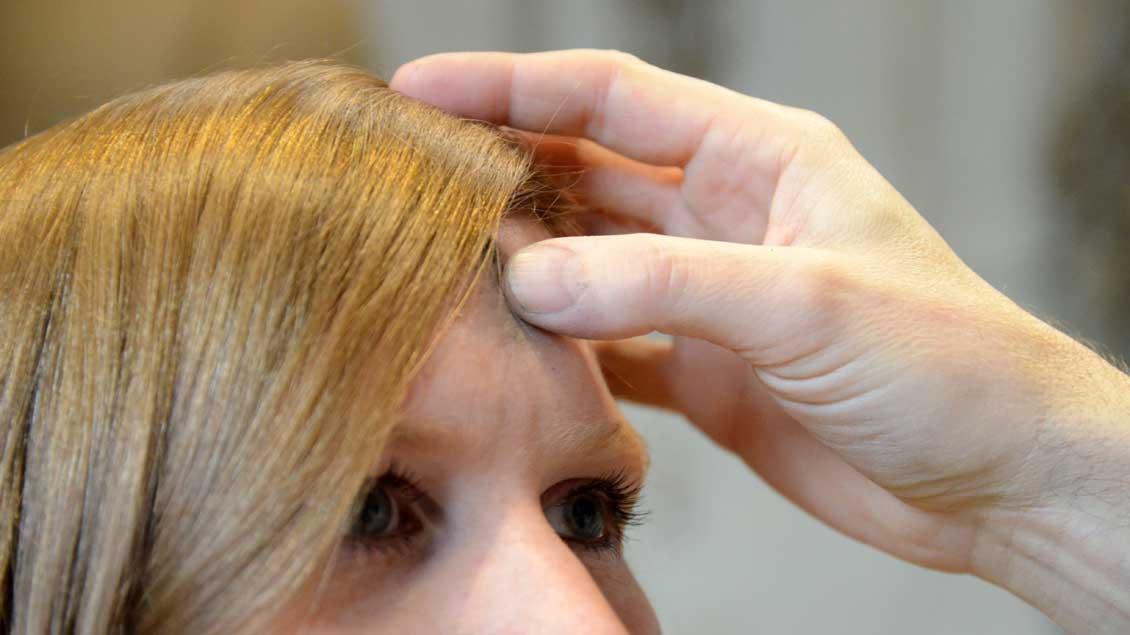 Eine Frau bekommt ein Aschekreuz auf die Stirn gezeichnet