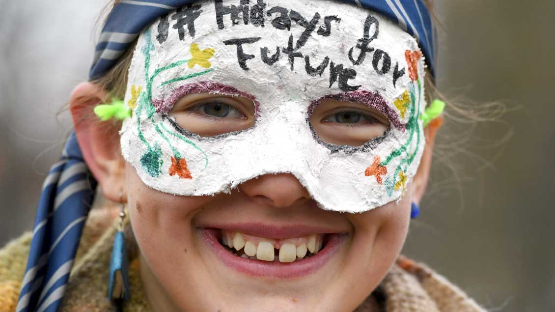 """Eine Schülerin mit einer Maske, auf der """"Fridays for Future"""" steht"""
