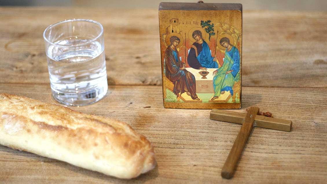 Auf einem Holztisch liegt ein Brot, daneben steht ein Glas mit Wasser. Auch ein Kreuz und ein Bild mit einer Szende der Emmaus-Jünger sind auf dem Tisch zu sehen.