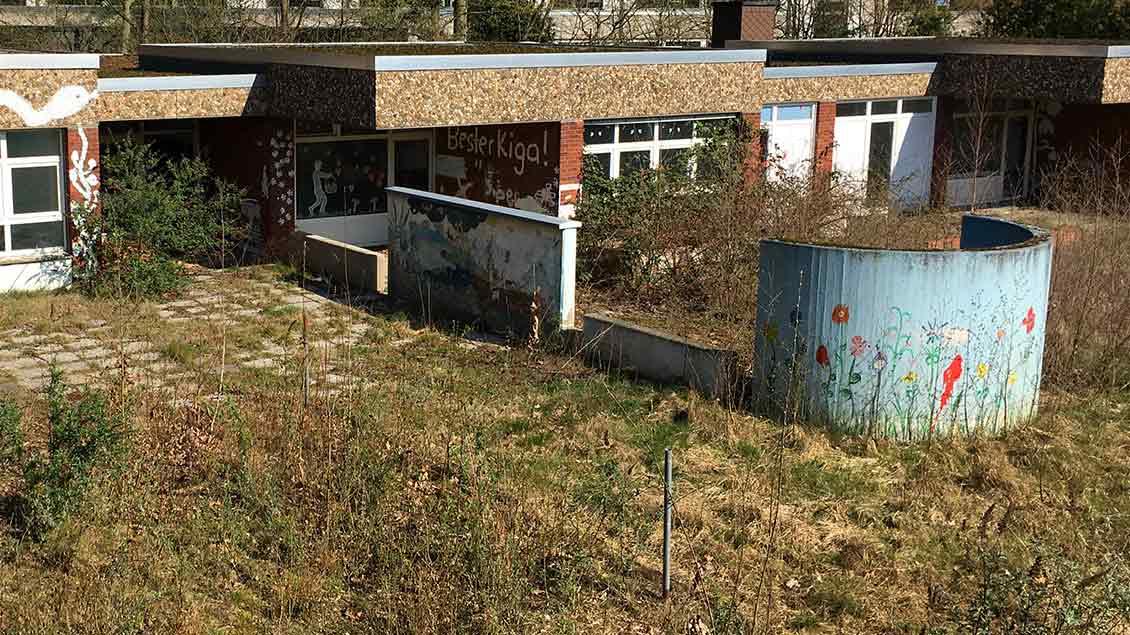 Ein heruntergekommender Kindergarten. Die Außenanlagen sind ungepflegt. Der Rasen vor dem Gebäude wuchert.