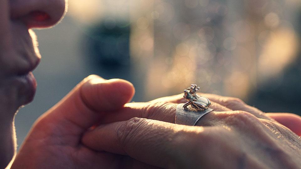 Frau küsst Ring mit Froschkönig.