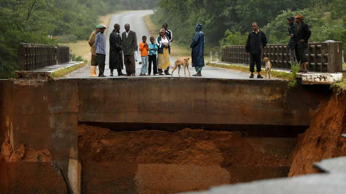 Bewohner stehen vor den Überresten einer Brücke über den Umvumvu-Fluss. Der Zyklon Chimanimani hat in weiten Teilen die Infrastruktur zerstört.