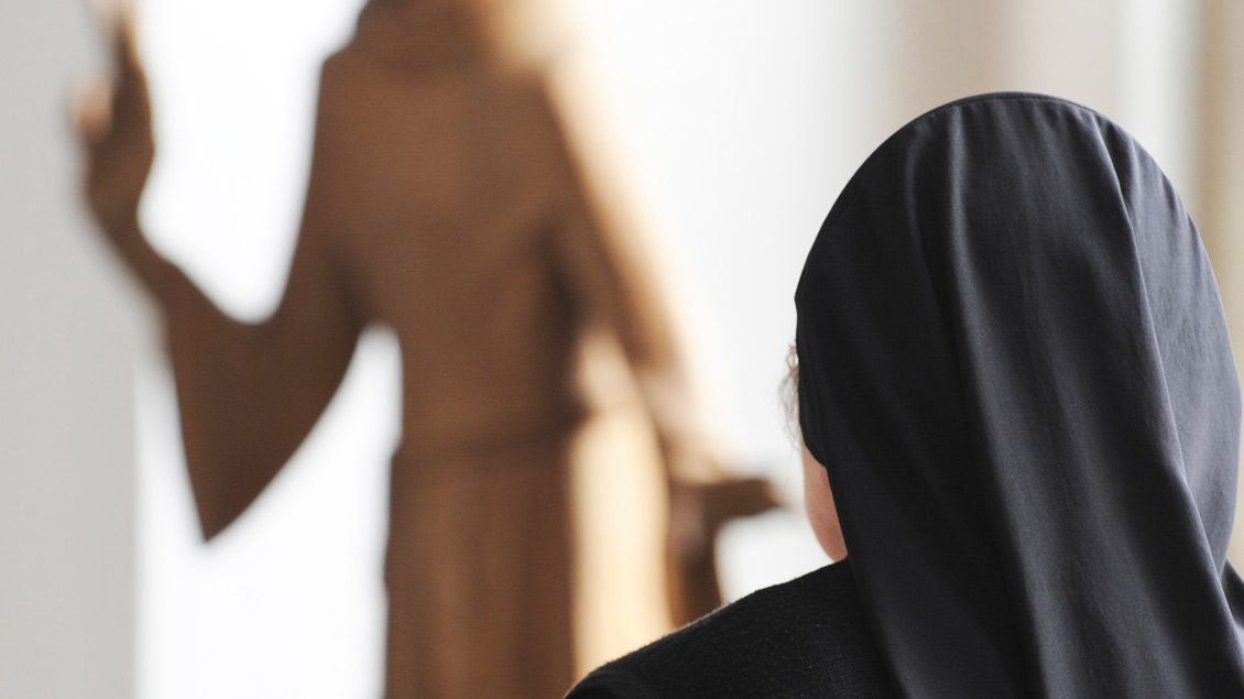 Ordensfrau sitzt in Kirchenbank.