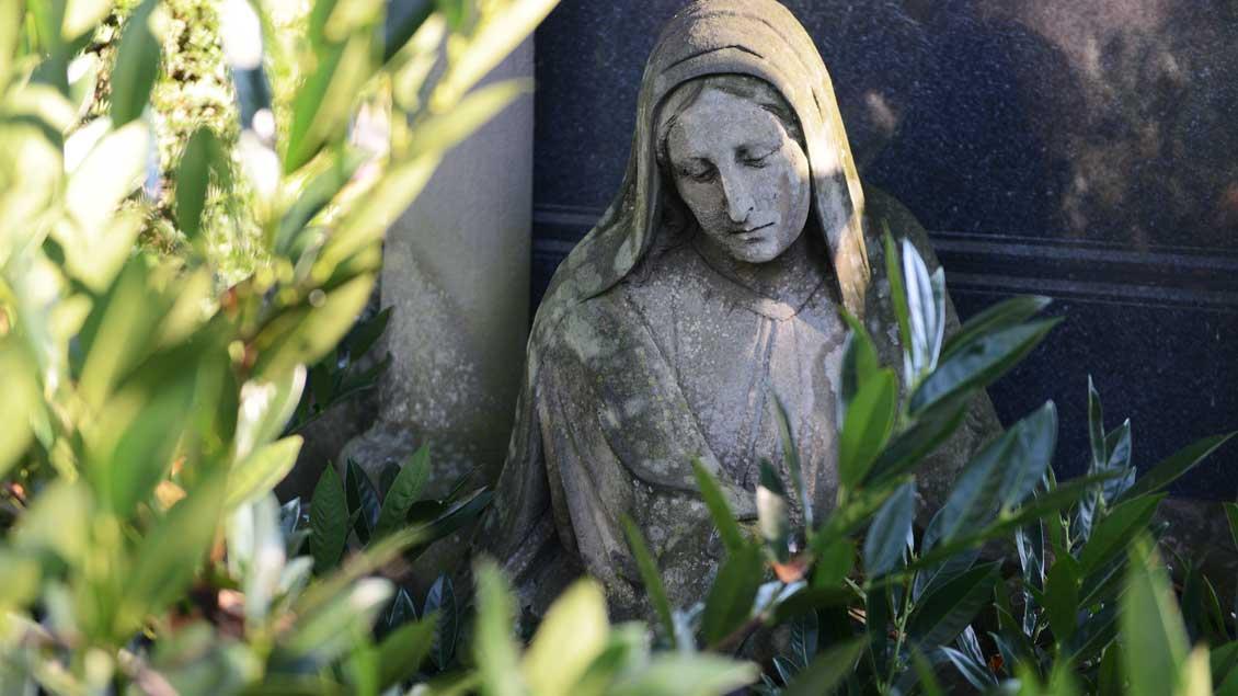 Marienfigur auf einem Friedhof.