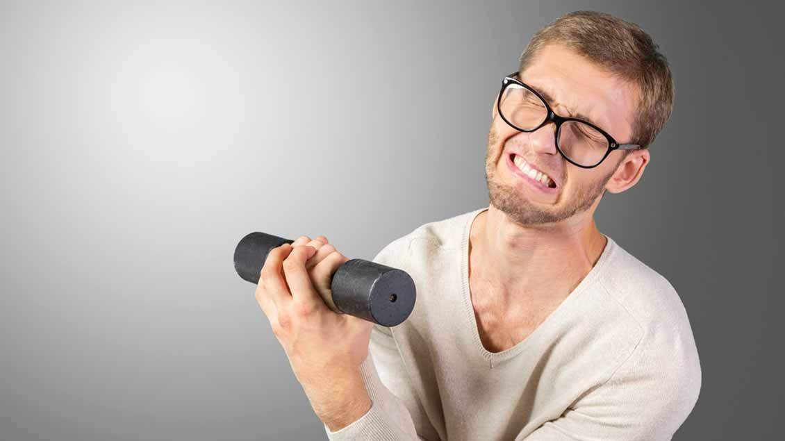 Ein Mann versuscht, Gewichte zu heben.