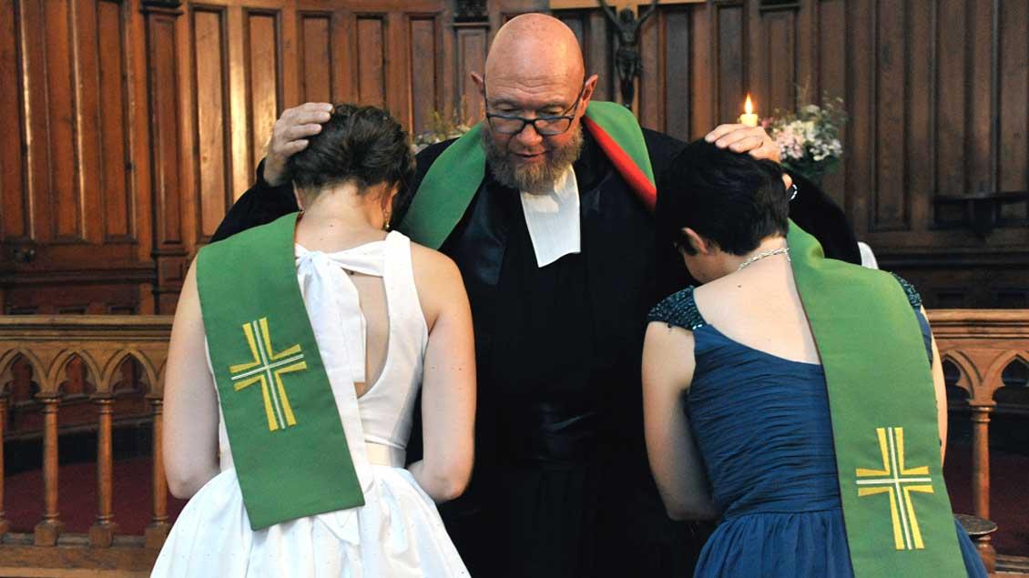 Ein protestantischer Pastor segnet zwei Bräute.