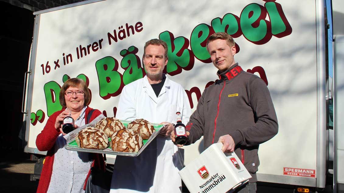 Misereror-Unterstützerin Maria Voß, Bäckermeister Klaus Hövelmann und Robert Dickhöver vom Supermarkt Rewe Kramer (rechts) präsentieren das Soli-Brot und das alkoholfreie Misereor-Fastenbier