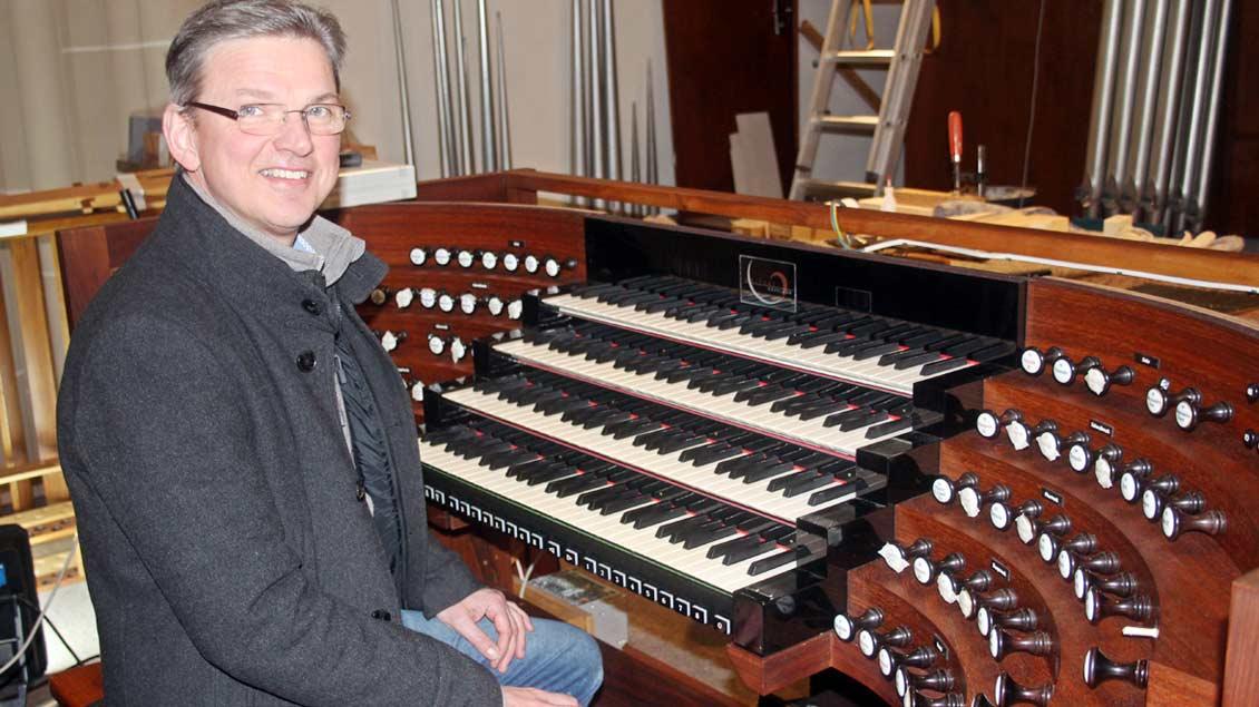 Kirchenmusiker Stefan Eicholt sitzt am Spieltisch der erweiterten Kirchenorgel.