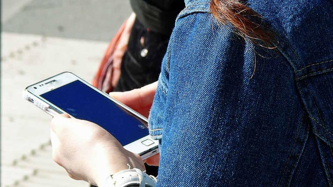 Ein Mädchen schaut auf ihr Handy, das sie in der Hand hält.