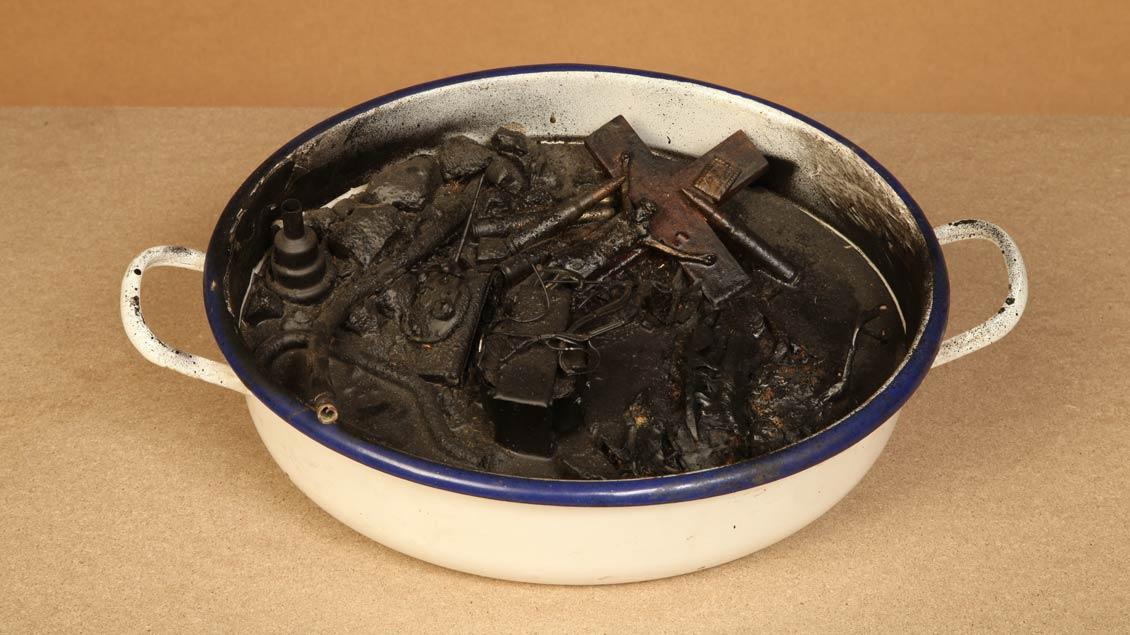 Ein Holzkreuz schwimmt in einer Suppe aus Öl.
