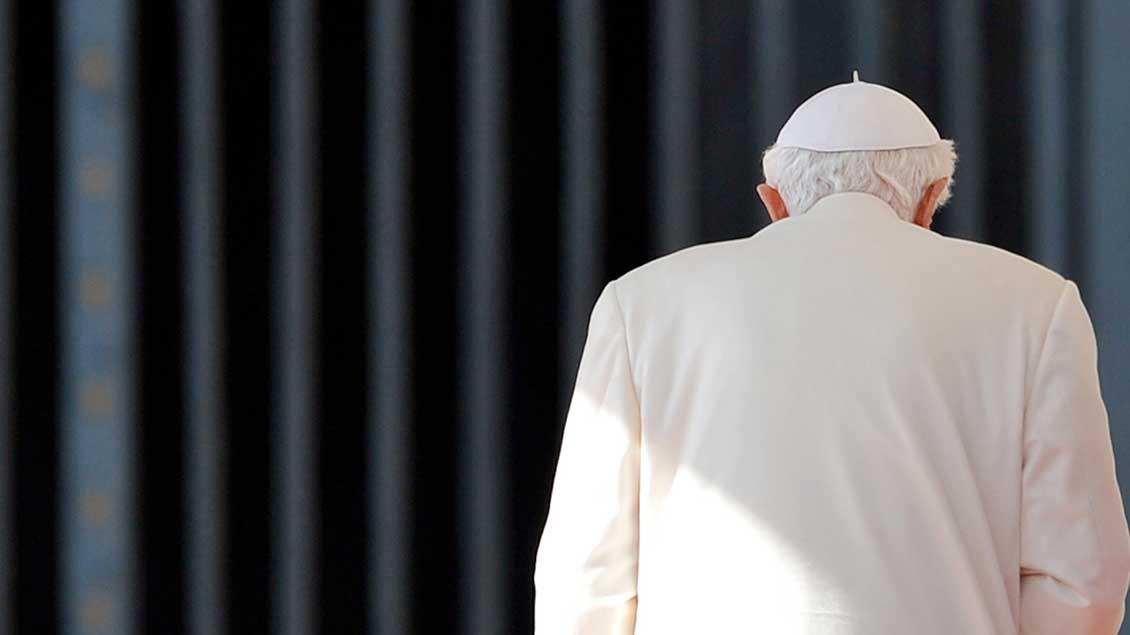 Der emeritierte Papst Benedikt XVI. vor einem Gitter von hinten fotografiert.