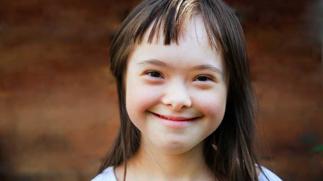 Ein lächelndes Kind mit Down-Syndrom