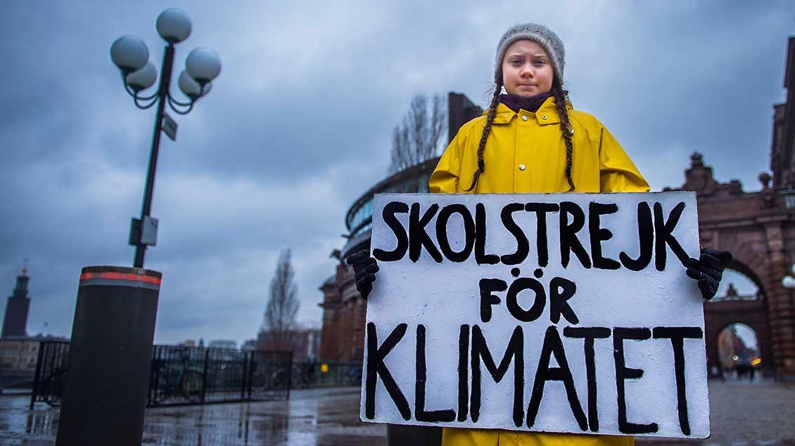 """Greta Thunberg im gelben Regenmantel mit einem Schild """"Schulstreik für das Klima""""."""