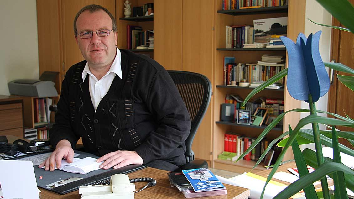 Pfarrer Heinrich Hagedorn sitzt an seinem Schreibtisch.