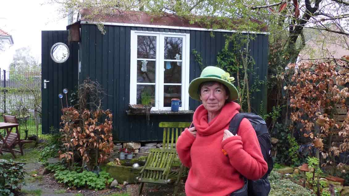 Eine Frau steht vor dem Bauwagen im Garten der Fanilie Sander