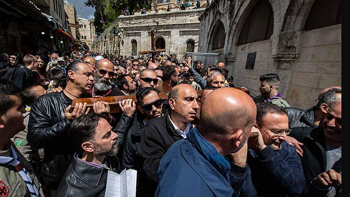 Männer tragen ein großes Holzkreuz beim Kreuzweg an Karfreitag 2019 auf der Via Dolorosa in Jerusalem.