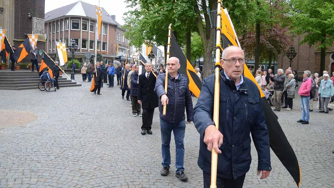 Männer ziehen mit Kolpingfahnen über den Kapellenplatz.