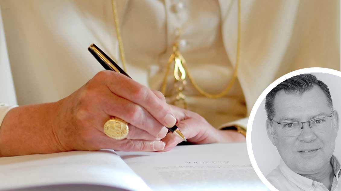 Papst Benedikt XVI. unterschreibt ein Dokument. Foto: KNA