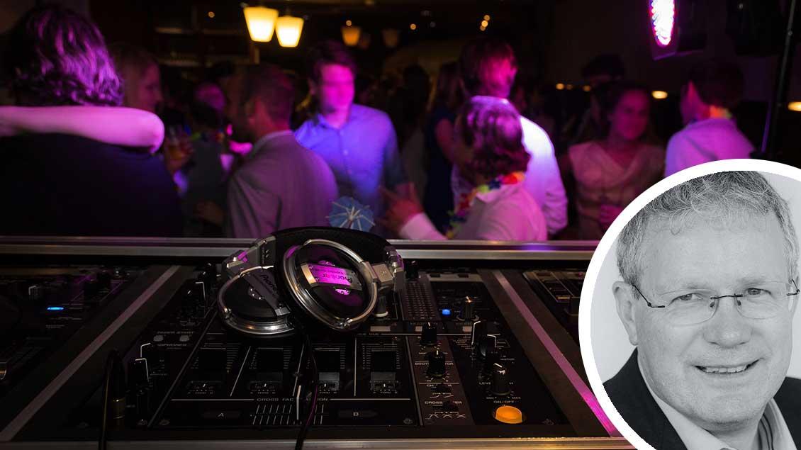 Szene aus einer Disco: Im Vordergrund das Mischpult eines DJs, im Hintergrund tanzende Menschen.