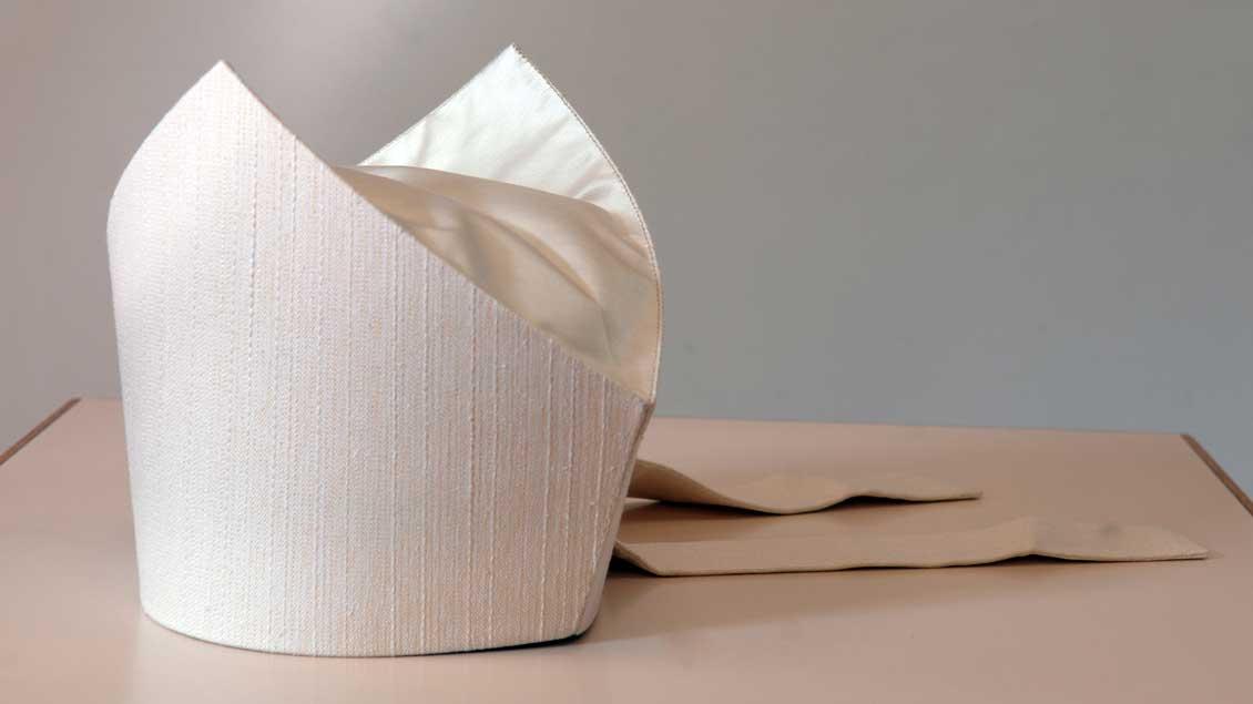 Eine weiße Mitra auf einem Tisch.