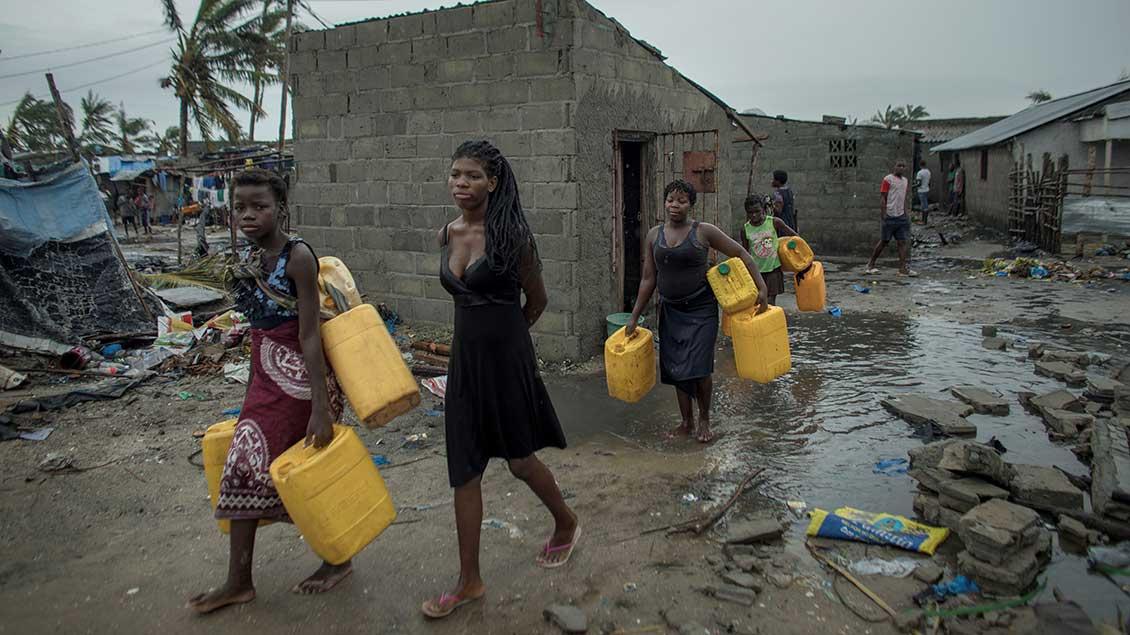 Frauen und Kinder tragen Wasser-Kanister durch ein überschwemmtes Dorf in Mosambik.
