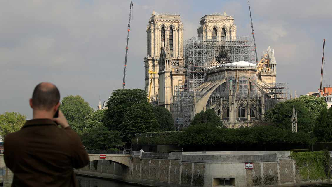 Ein Mann fotografiert Reparaturarbeiten am 29. April an Notre-Dame in Paris. Foto: Reuters