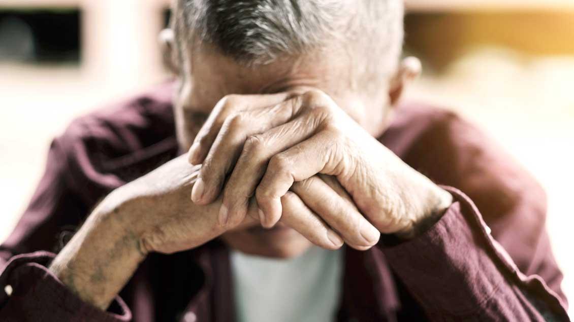 Ein Mann stützt frustriert seinen Kopf auf seine Hände.