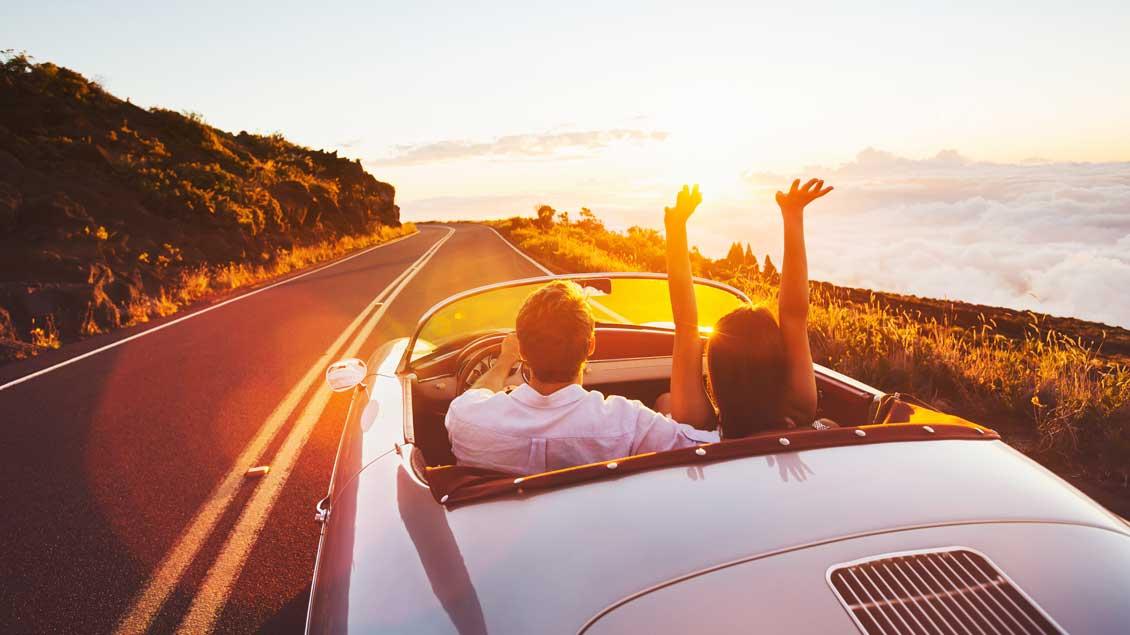 Ein Paar fährt in einem Cabriot in den Sonnenuntergang.
