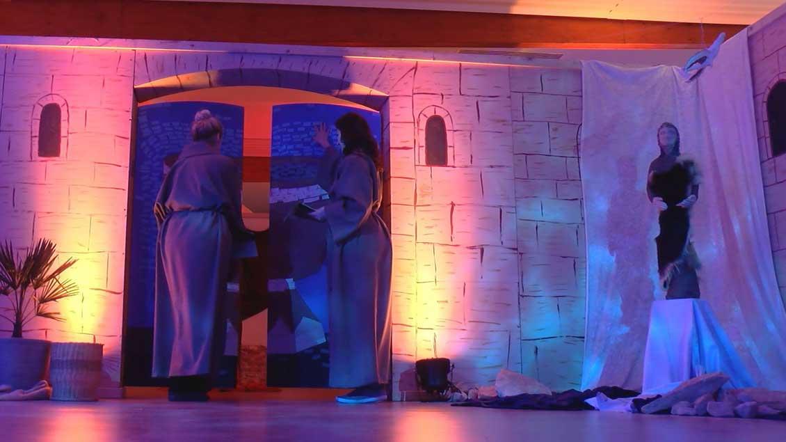 Pastoralreferentin Stefanie Eißing und Pastoralassistentin Jasmin Laudano öffnen das Tor mit dem Taufbrunnen am Eingang des Ostergartens in Schöppingen.