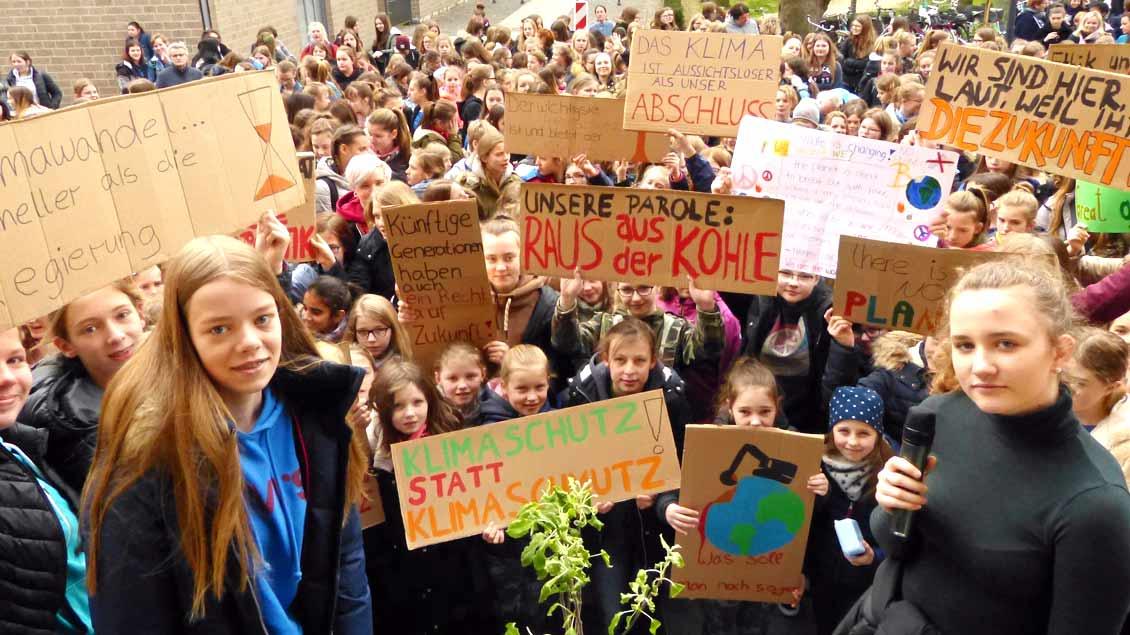 SChülerinnen der Marienschule in Xanten halten Plakate zum Klimaschutz hoch.