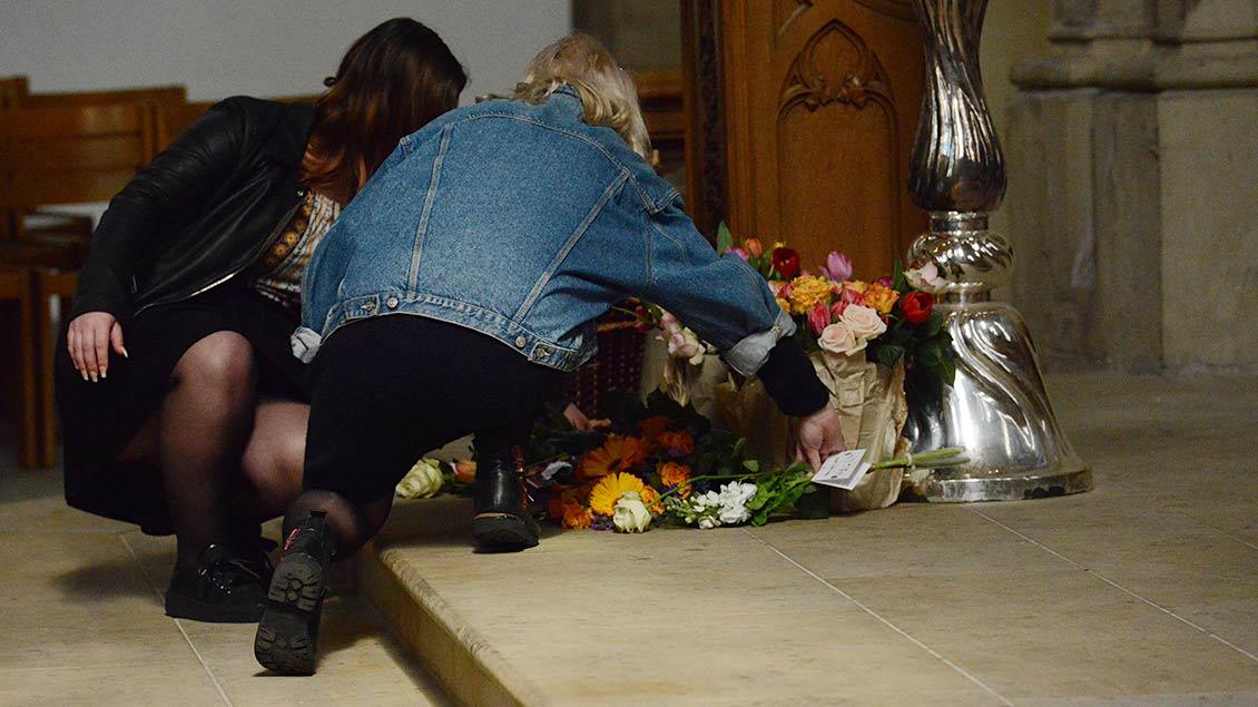 Angehörige legen Blumen vor die Osterkerze in der St.-Lamberti-Kirche.   Foto: Michael Bönte
