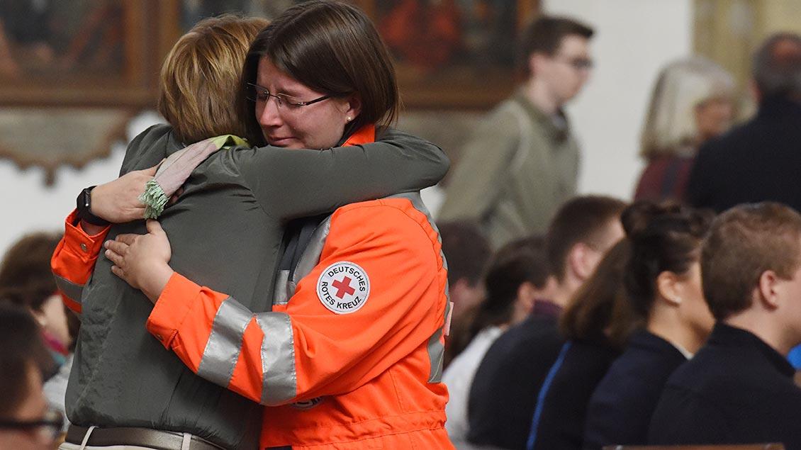 Trorst: Eine Mitarbeiter eines Rettungsdienstes umamrt in der St.-Lamberti-Kirche eine trauernde Angehörige.   Foto: Michael Bönte