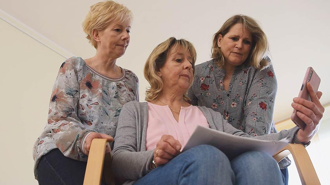 Die drei Schwestern der Verstorbenen blicken auf ein Handy-Foto der Verstorbenen.