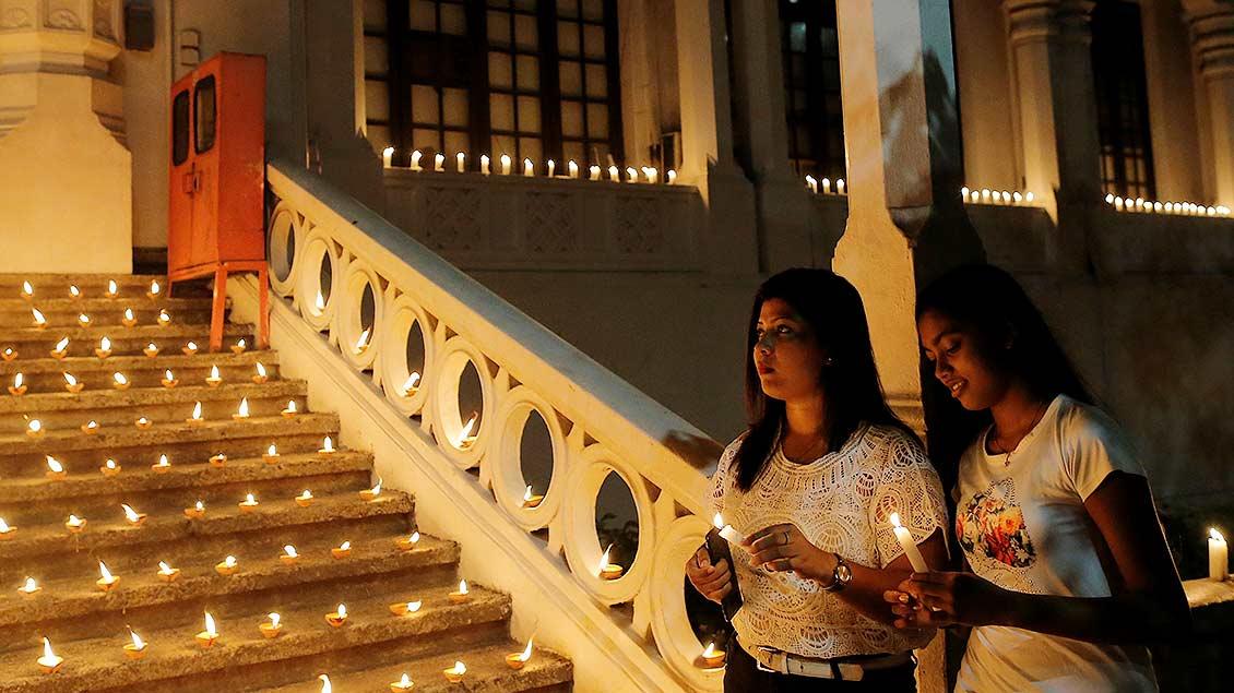 Zwei Frauen halten während einer Vigilfeier Kerzen in den Händen.