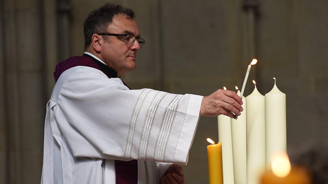 Pfarrer Hans-Bernd Köppen entzündet vier Kerzen auf dem Altar der St.-Lamberti-Kirche in Münster.
