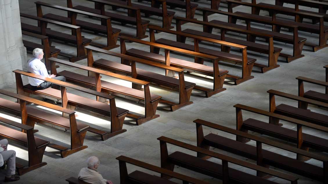 Wenige Menschen sitzen in Kirchenbänken