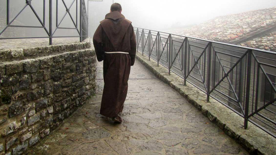 Ein Mönch geht allein im Nebel