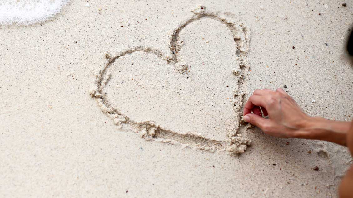 Ein Finger zeichnet ein Herz in den Sand.