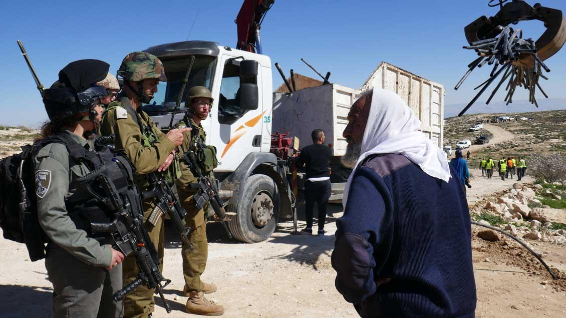 Israelische Soldaten konfiszieren Wasserleitungen in Masafer Yatta, ein Schäfer kommt dazu.